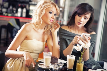 telephone together: Two women using a smartphone