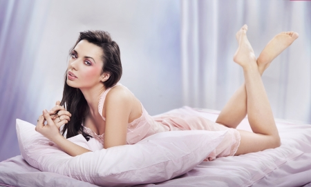 Adorable brunette posing on a comfortable bed photo