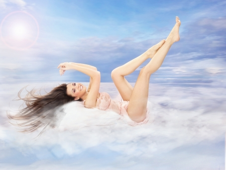 Sexy young beauty lying on clouds