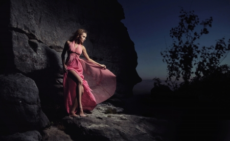 woman night: Glamour woman standing next to a rock