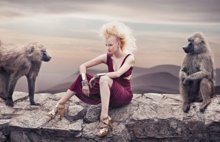 Blond beauty posing with monkeys photo