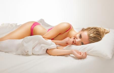 femme en sous vetements: Sourire femme couch�e sur le lit