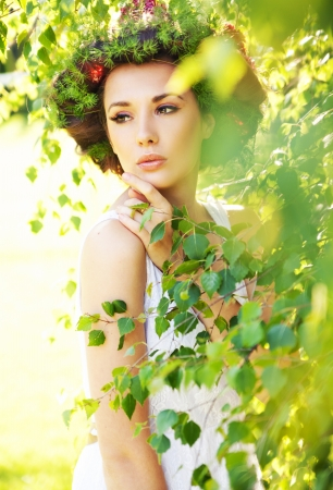 Young beauty among greenery photo
