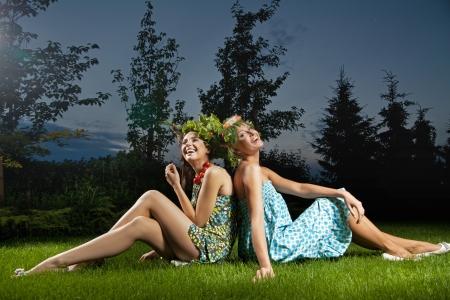 Two smiling girls sitting in a beautiful garden photo