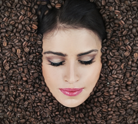 Beautiful face among coffee beans Stock Photo - 15865179