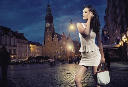 urban fashion: Sexy young beauty posing over night city background Stock Photo