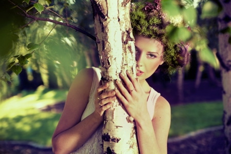 Beautiful girl behind the tree photo