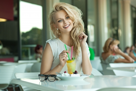 Young cheerful blonde in a drink bar photo