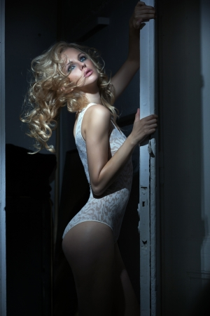 woman lingerie: Sexy blonde in dark room Stock Photo