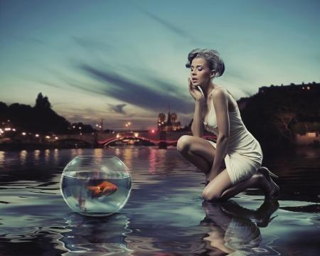 mujer elegante: Belleza mujer con peces de oro