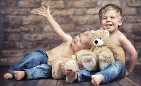 hermanos jugando: Dos hermanos felices que juegan los juguetes Foto de archivo