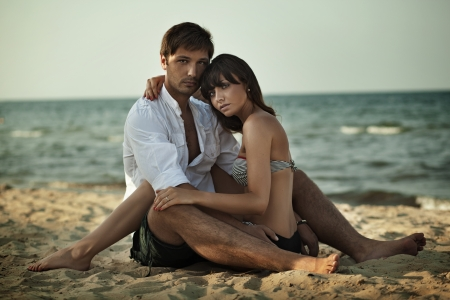 attractive couple: Young woman hugging on a beach