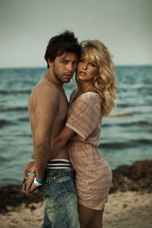 pareja abrazada: Atractiva pareja abraz�ndose en un paisaje rom�ntico Foto de archivo