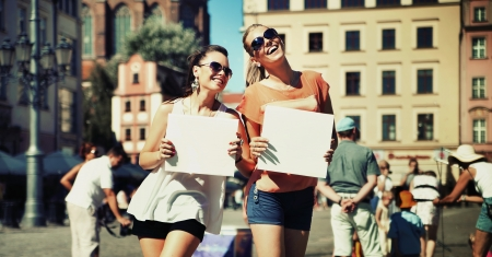 Two smiling girls holding empty board photo