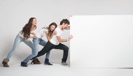Young happy people pushing white board photo