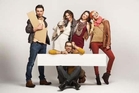 grupo de hombres: Grupo de amigos sosteniendo anuncio tablero blanco Foto de archivo