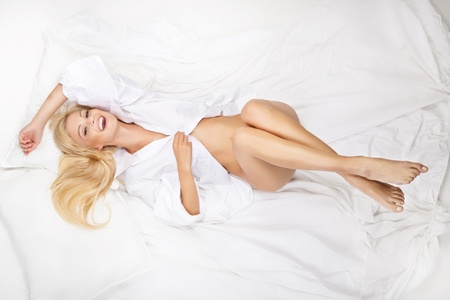 Portrait of blonde beautiful woman on bed photo