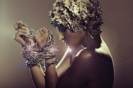 Attractive young lady trying to cast off chains Stock Photo - 16614370
