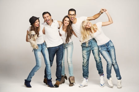 women in jeans: Smiling group of young friends with dog Stock Photo