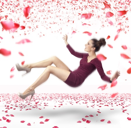 Attractive lady falling down over rose petals in background