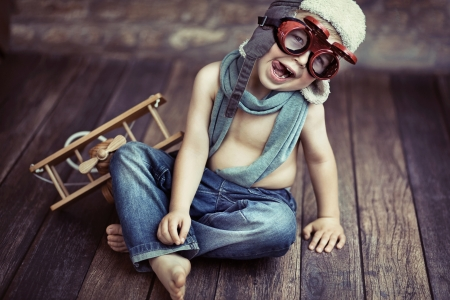 Picture of small boy playing wooden plane photo