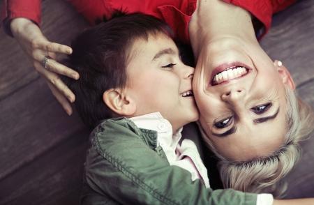 madre soltera: Muchacho joven que besa a su madre sonriente Foto de archivo
