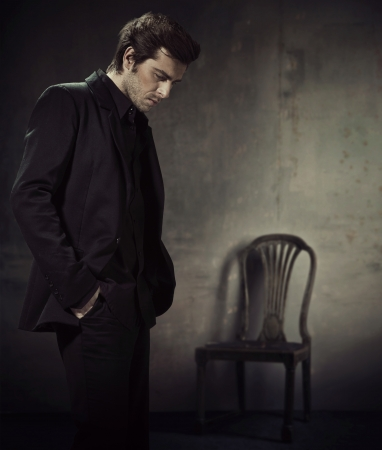 young man portrait: Handsome and calm man in a business suit on a dark background