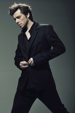 Young confident man wearing black suit