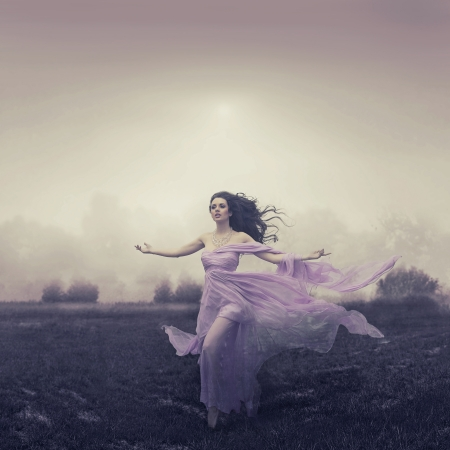 evening dress: Portrait of beautiful woman running over the field
