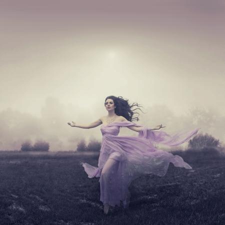 vestido de noche: Retrato de la mujer hermosa que corre sobre el campo