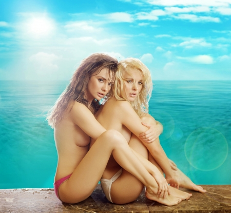 two and a half: Two young half-nude female friends over the colorful background Stock Photo