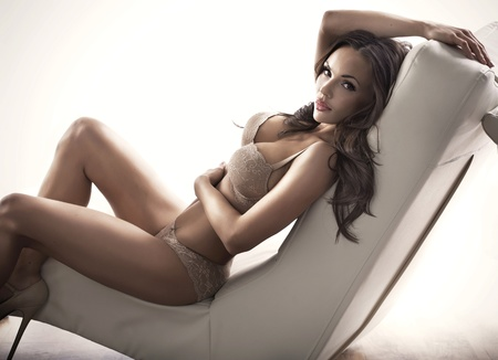 sexy lingerie: Adorable brunette woman on the modern couch Stock Photo