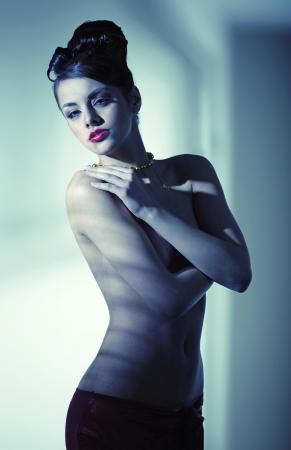 naked young girl: Half-naked pretty woman with bun haircut Stock Photo
