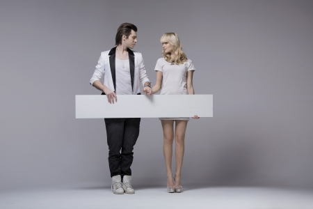 women and men: Picture presenting attractive young couple with board Stock Photo