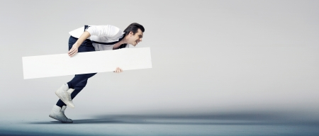 advertising board: Elegant young man running with a white board Stock Photo
