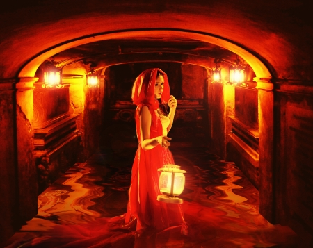 Romantic lady in red holding big lantern in a dark dungeon photo