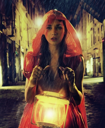 Innocent girl in red holding the lantern photo