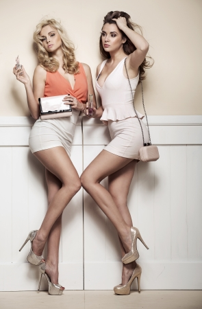 sexy girls party: Adorable girlfriends with sexy legs posing against to the wall Stock Photo