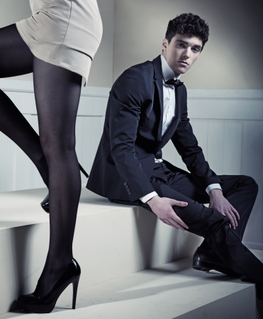 Young handsome man looking at sexy long legs  photo