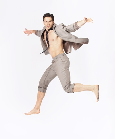 Handsome jumping guy on suit isolated on a white background photo
