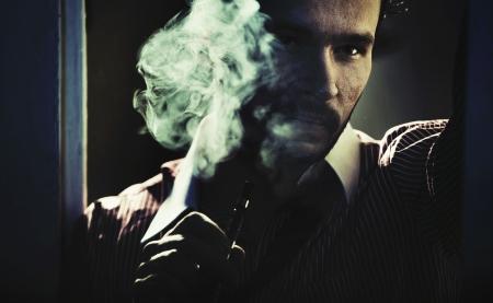 Smoking handsome guy with seus look Stock Photo - 19566478