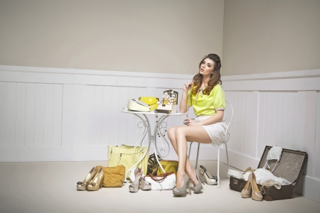 elegance fashion girls look sensuality young: Confused young lady among shoes Stock Photo