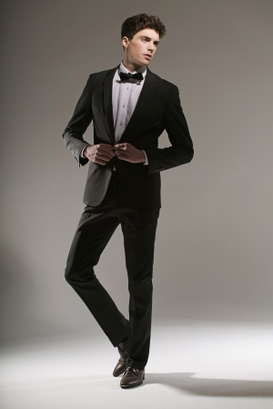 male fashion model: Apuesto joven tratando de bot�n de la chaqueta