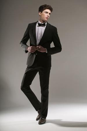 donne eleganti: Handsome giovane uomo che cerca di abbottonarsi la giacca
