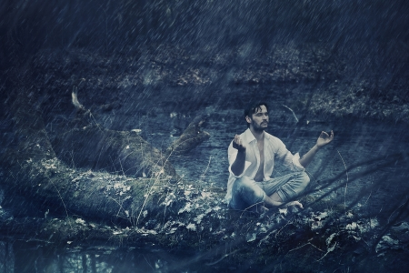 Art photo of handsome guy meditating in the rain photo