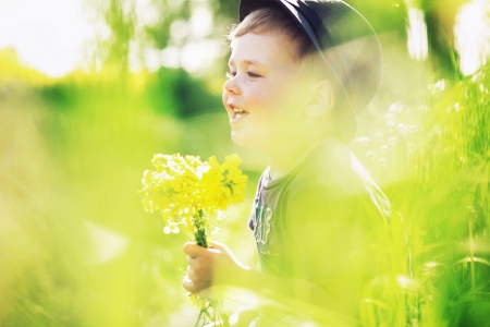 bright eyed: Smiling kid holding yellow flowers
