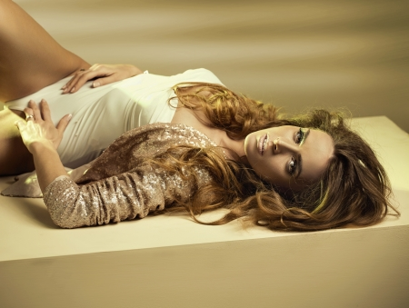 Alluring young lady lying down on the floor photo