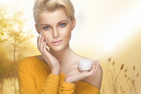 Portrait of young lady applying moisturizer cream on her pretty face photo