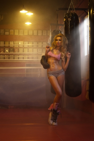 Young blonde female boxer with leather gloves photo