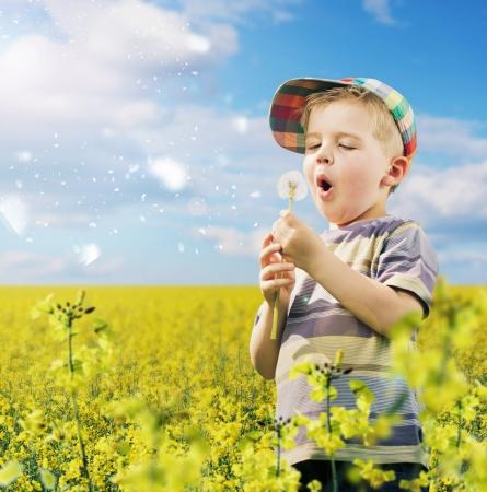 Cute kid playing dandelions on the meadow